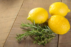Lemons and herbs on a wooden table Stock Images