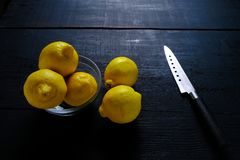 Lemons and knife on cutting board on wooden table Stock Images