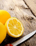 Lemons and knife. On wooden board. Royalty Free Stock Photos