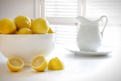 Lemons in large bowl on table Stock Images
