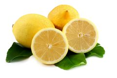 Lemons on Leaves. Whole and cut lemons, on lemon leaves, isolated on white stock photo