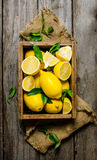 Lemons with leaves in a box on the fabric. On wooden background. Stock Photography