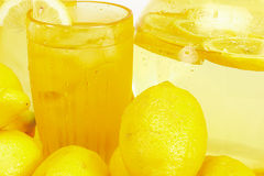 Lemons and Lemonade. A pitcher and glass of lemonade with lemons around them Royalty Free Stock Photography