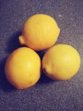 Three yellow lemons on the table royalty free stock photography