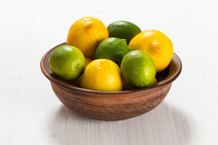 Lemons and limes in a clay bowl Stock Photo