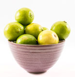 Lemons and limes composed in a violet cup on a white background Royalty Free Stock Photos