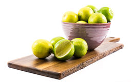 Lemons and limes composed in a violet cup, wooden board, on a white background - side  view Royalty Free Stock Image