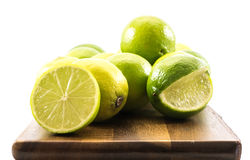 Lemons and limes composed on a wooden board and white background Stock Image