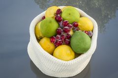 Lemons and Limes with Cranberrys. In a basket on a glass table with tree reflexion Royalty Free Stock Photo