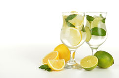 Lemons and limes in a glass with water  on white background Stock Images