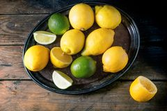 Lemons and limes. Heap of whole and sliced lemons and limes in vintage tray over wooden background. Top view Royalty Free Stock Photo