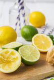 Lemons, limes, mint cocktail preparation on a wooden background Royalty Free Stock Photography