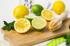 Lemons, limes, mint cocktail preparation on a wooden background Royalty Free Stock Photo