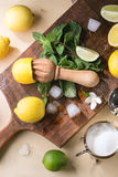 Lemons, limes and mint. Heap of whole and sliced lemons, limes and mint with citrus reamer, sugar and ice cubes on wooden cutting board over wooden background Royalty Free Stock Image