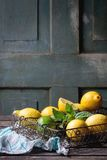 Lemons, limes and mint. Heap of whole and sliced lemons and limes with mint in vintage metal grid box over old wooden table with turquoise wooden background Stock Photo