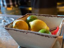 Lemons and limes with peeler sitting in bowl of a bar for bartenders to make cocktails royalty free stock image