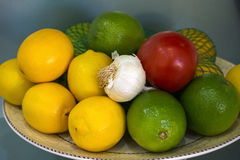 Lemons Limes Tomato Garlic Bowl net Royalty Free Stock Images
