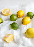 Lemons and limes on the white background: whole fruits and cross Royalty Free Stock Photos