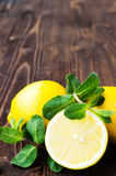Lemons with mint on wooden table Stock Image