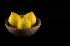 Lemons in a natural handmade real wood bowl isolated in black ba Royalty Free Stock Photos