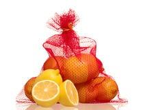 Lemons in net bag. Isolated on white background royalty free stock image