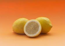 Lemons with orange background. Royalty Free Stock Photography