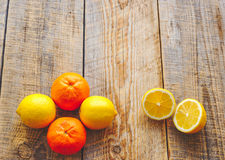 Lemons and oranges in  row on wodden table Stock Photos