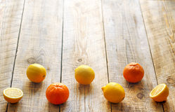 Lemons and oranges in staggered rows on wodden table Stock Photography