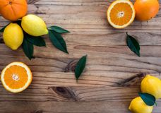 Lemons and oranges on the wooden table royalty free stock photography