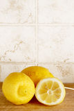 Lemons from organic farming, one cutted. A composition with some lemons from organic farming, one cutted, on a wooden cutting board, inside a kitchen with tiles stock images