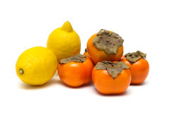 Lemons and persimmons isolated on white background Royalty Free Stock Photos