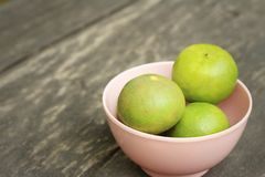 Lemons in a pink bowl on a wood background Stock Images