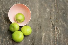 Lemons in a pink bowl on a wood background Stock Photo