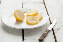 Lemons in a plate and knife on wood table. Lemons in a plate on wood table with knife Stock Photo