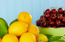 Lemons And Ripe Red Cherries In Green Colander Royalty Free Stock Photo