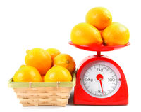 Lemons on scales and in a basket. Royalty Free Stock Image