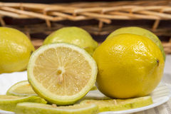 Lemons and slices in front of a wicker basket Stock Photos