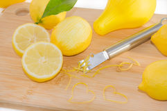 Lemons, squeezer, zest and Zester on wooden cutting board. Royalty Free Stock Photography