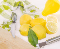 Lemons, squeezer, Zester, knife and wooden cutting board. Stock Photo