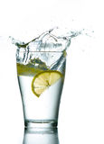 Lemons. Three lemons are falling into the glass of water Stock Image
