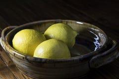 Lemons. Three yellow lemons in a dish Stock Photo