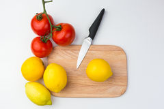 Lemons, Tomatoes, and Knife on Wooden Cutting Board Royalty Free Stock Photo
