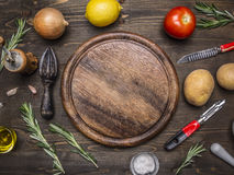 Lemons, tomatoes, onions, potatoes, rosemary, knife for peeling potatoes laid around  round cutting board place text,fram Royalty Free Stock Image