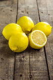 Lemons on top of a table. Lemons with cut lemons on a table royalty free stock photography