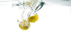 Lemons in water. Lemons falling into Water creating a vortex with a splash Stock Images