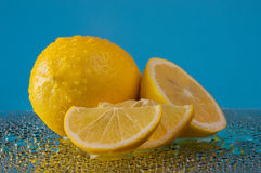 Lemons in water drops on a blue background Stock Image