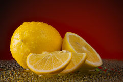 Lemons in water drops on a red background Stock Photo
