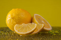 Lemons in water drops on a yellow background Stock Photography