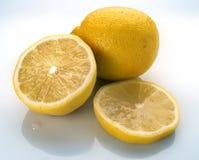 Lemons on white. Whole half sliced lemons on white Royalty Free Stock Photo