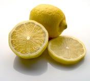 Lemons on white. Whole half sliced lemons on white Royalty Free Stock Photos